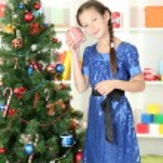 Little girl holding gift box near christmas tree — Stock Photo #17844569