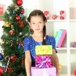 Little girl holding gift box near christmas tree — Stock Photo #17844573