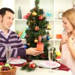 Young happy couple with presents sitting at table near Christmas tree — Stock Photo #17844677