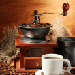 Stock Photo: Coffee grinder, turk and cup of coffee on brown wooden background