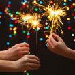 Stock Photo: Beautiful sparklers in woman hands on garland background