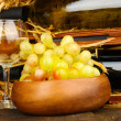 Wooden case with wine bottles, wineglass and grape close up — Stock Photo