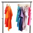 Stock Photo: Choice of clothes of different colors on wooden hangers, isolated on white