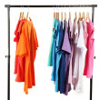 Choice of clothes of different colors on wooden hangers, isolated on white — Stock Photo