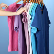 Variety of casual shirts on wooden hangers,on blue background — Stock Photo #17845575