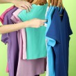 Variety of casual shirts on wooden hangers,on green background — Foto Stock