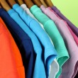 Variety of casual shirts on wooden hangers,on blue background - Stockfoto