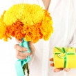Woman holds a box with a gift and flowers on white background close-up — Foto Stock