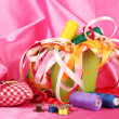 Color bucket with multicolor ribbons and thread on pink fabric background — Foto Stock