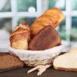 Fresh bread in basket on wooden table on window background — Stock Photo