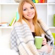 Attractive young woman sitting on sofa, holding cup with hot drink, on home interior background — Stock Photo