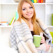 Attractive young womsitting on sofa, holding cup with hot drink, on home interior background — Stock Photo #17847771