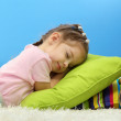 Cute little girl sleeping on colorful pillows, on blue background — Stock Photo #17848067