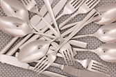 Forks, knifes and spoons on grey mat close-up — Stock Photo