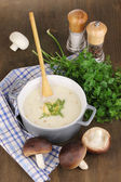 Mashed potatoes in saucepan with ingredients on wooden table — Stock Photo