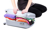 Girl tries to close the suitcase isolated on white — Stock Photo