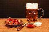 Bier und gegrillten würstchen auf holztisch auf braunen hintergrund — Stockfoto