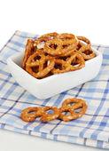Tasty pretzels in white bowl isolated on white — Stock Photo