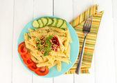 Rigatoni pasta dish with tomato sauce on white wooden table — Stock Photo