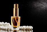 Women's perfume in beautiful bottle and beads, on black background — Stock Photo