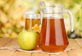 Fullt glas och kanna av äppeljuice och äpple på träbord utomhus — Stockfoto