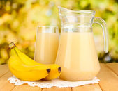 Full glass and jug of banana juice and bananas on wooden table outdoor — Stock Photo