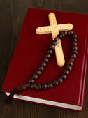 Bible, rosary and cross on wooden table close-up — Stock Photo