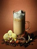 Perfumado café latte em copo de vidro com especiarias, sobre fundo marrom — Foto Stock