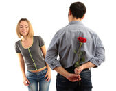 Loving man holding red rose for his woman isolated on white — ストック写真