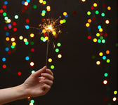 Beautiful sparkler in woman hand on garland background — Stock Photo
