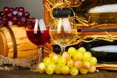 Dřevěné pouzdro s lahví vína, barel, skleničku a hroznů na dřevěný stůl na šedém pozadí — Stock fotografie