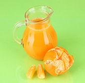 полный кувшин мандариновый сок, на деревянных цвет фона — Стоковое фото