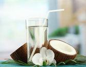 Noce di cocco con un bicchiere di latte, sul tavolo di legno blu — Foto Stock