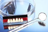 Prótesis con herramientas dentales sobre fondo azul — Foto de Stock