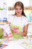 молодая девушка сушит блюда на кухне — Стоковое фото
