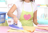 Young girl ironing in room — Stock Photo