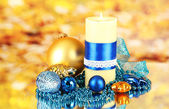 Yellow candle with christmas decoration on bright background — Stock Photo