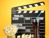 Movie clapperboard, cola and popcorn on orange background — Stockfoto