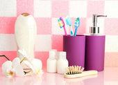 Koupelnové doplňky na poličce v koupelně na pozadí zdi růžový dlaždic — Stock fotografie