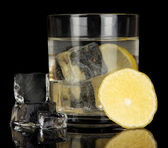 Ice cubes in glass with lemon isolated on black — Stock Photo