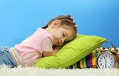 Cute little girl sleeping on colorful pillows, on blue background — Stock Photo