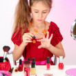 Little girl in her mother's dress, is trying painting her nails — Stockfoto