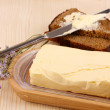 Butter on wooden holder and bread on wooden table close-up — Stock Photo