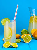 Citrus lemonade in pitcher and glass of citrus around on wooden table on blue background — Stock Photo