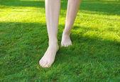 Legs walking on green lawn — Stock Photo