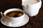 A cup of strong coffee and sweet cream on coffee beans close-up — Stock Photo
