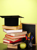 Books and magister cap against school board on wooden table on green background — Foto Stock