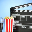 Movie clapperboard, cola and popcorn on blue background - Stok fotoğraf
