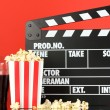 Movie clapperboard, cola and popcorn on red background - Stok fotoğraf