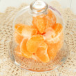 Tangerine on saucer under glass cover on light background — Stock Photo
